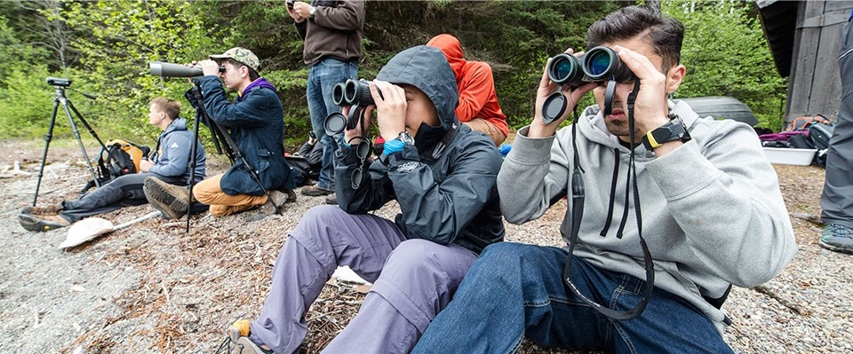 several people in hoodies and warm clothes with binoculars